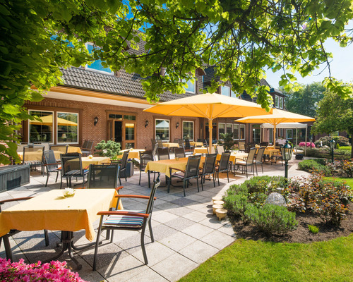 Terrace with sunshades overlooking the beautiful green grounds at the 4-star-superior hotel Ringhotel Celler Tor in Celle