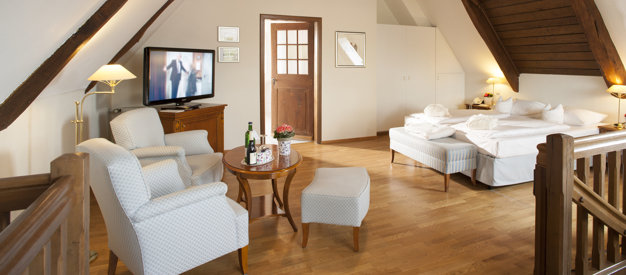Suite over two floors connected with wooden stairs at the 4-star-superior hotel Ringhotel Landhaus Eggert in Muenster