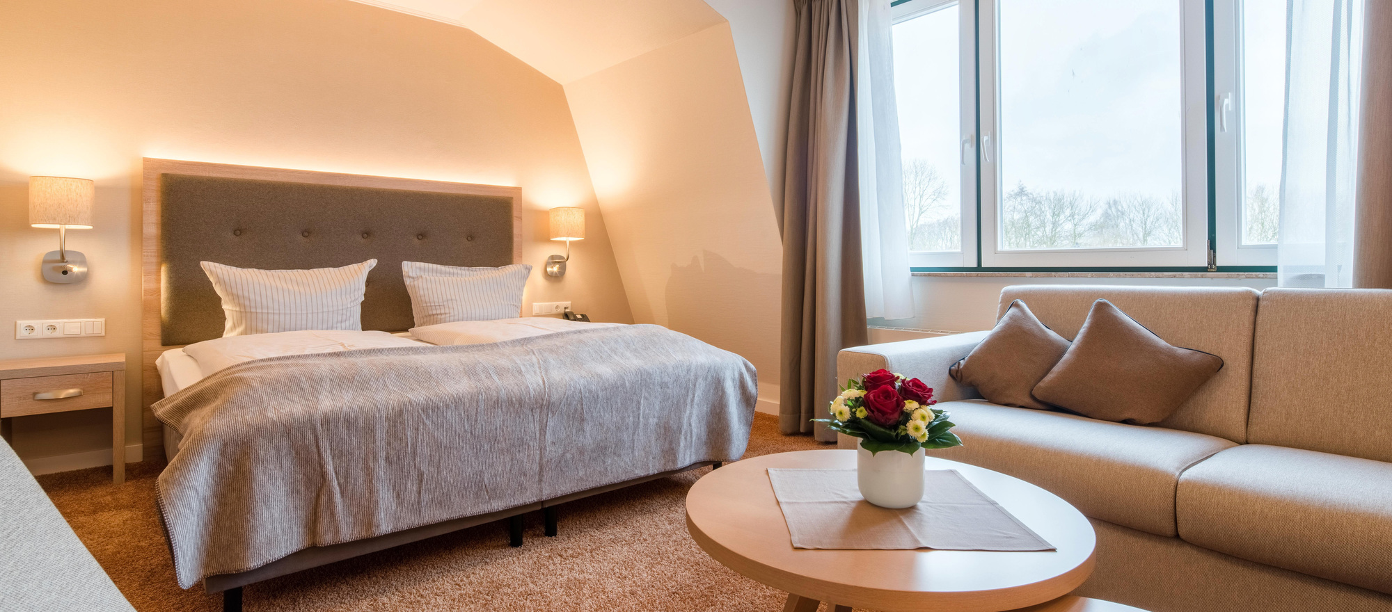 Deluxe Room with cozy sofa corner at the 4-star hotel Ringhotel Altes Zollhaus in Horumersiel