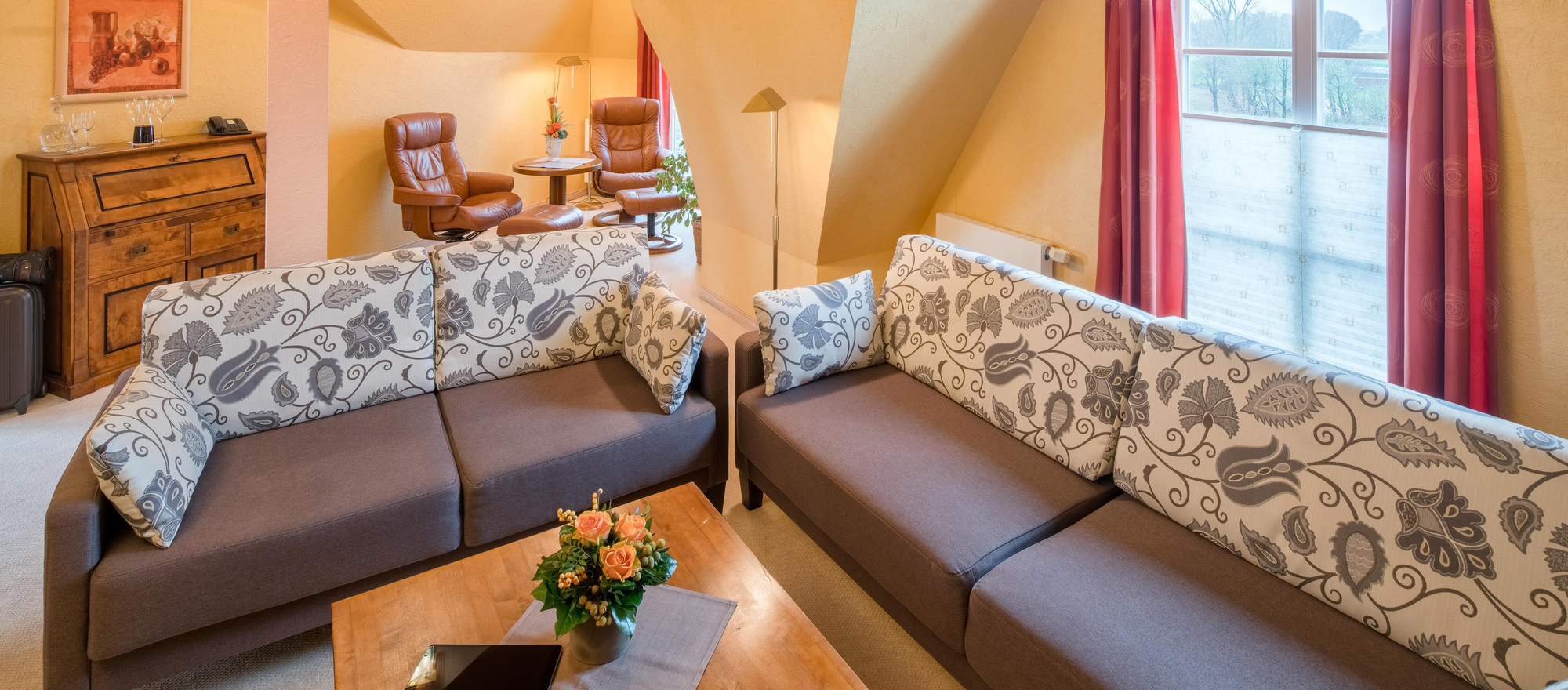 Spacious room with living room couch at the 4-star hotel Ringhotel Altes Zollhaus in Horumersiel