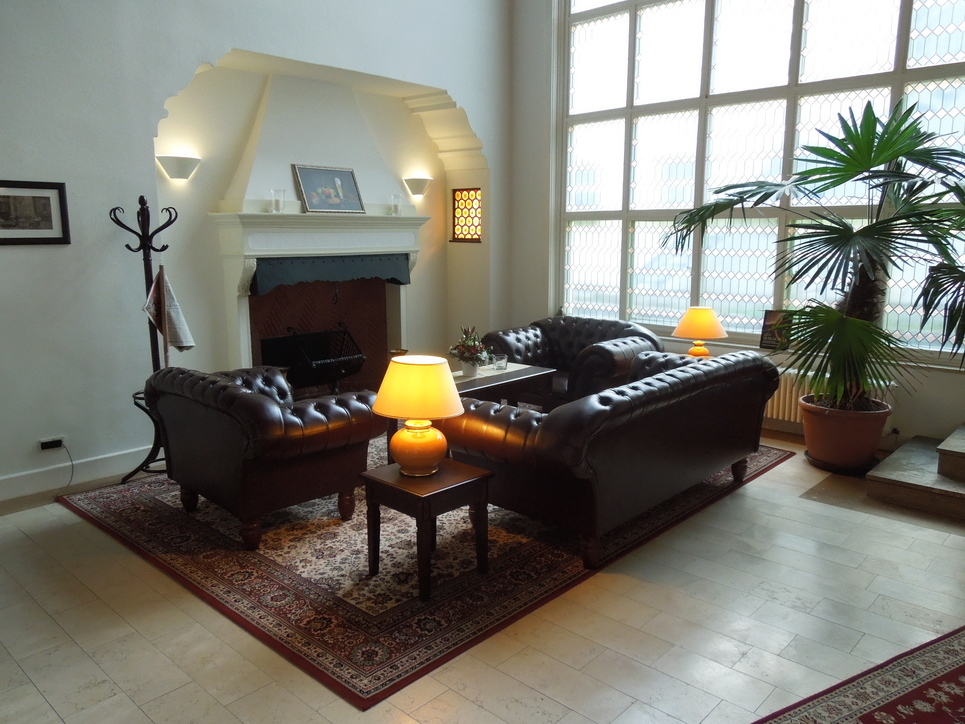 Fire place lounge with luxury dark leather sofa at the hotel Ringhotel Mutiger Ritter in Bad Koesen
