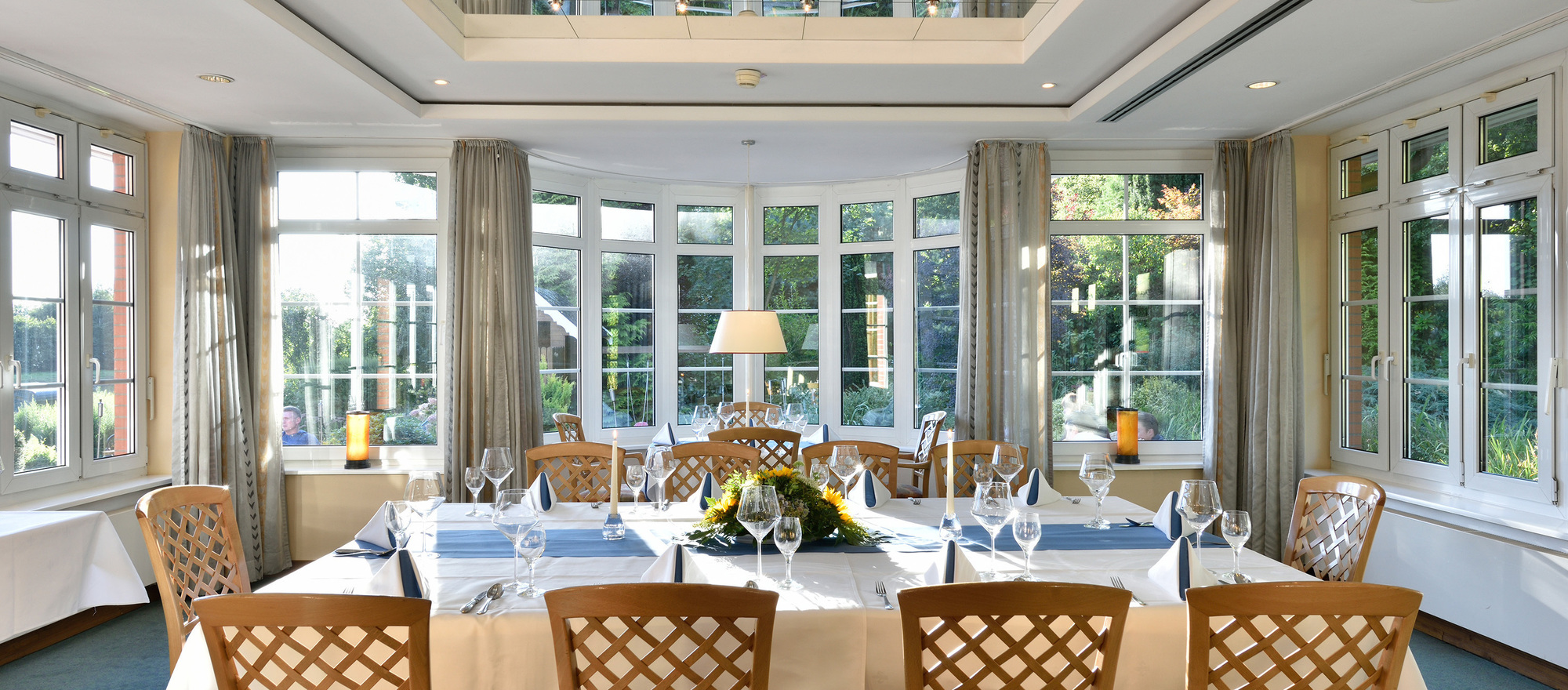 Winter garden restaurant overlooking the garden in Ringhotel Koehlers Forsthaus in Aurich, 4-star hotel at the North Sea coast