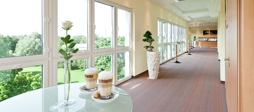 Conference lounge area with view into the green surrounding in the 4-star hotel Ringhotel Am Stadtpark in Luenen