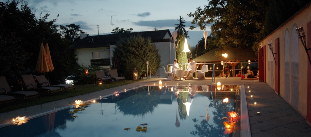 Outdoor pool of the 3-star-superior Ringhotel Aparthotel Badblick garni in Bad Bellingen by night