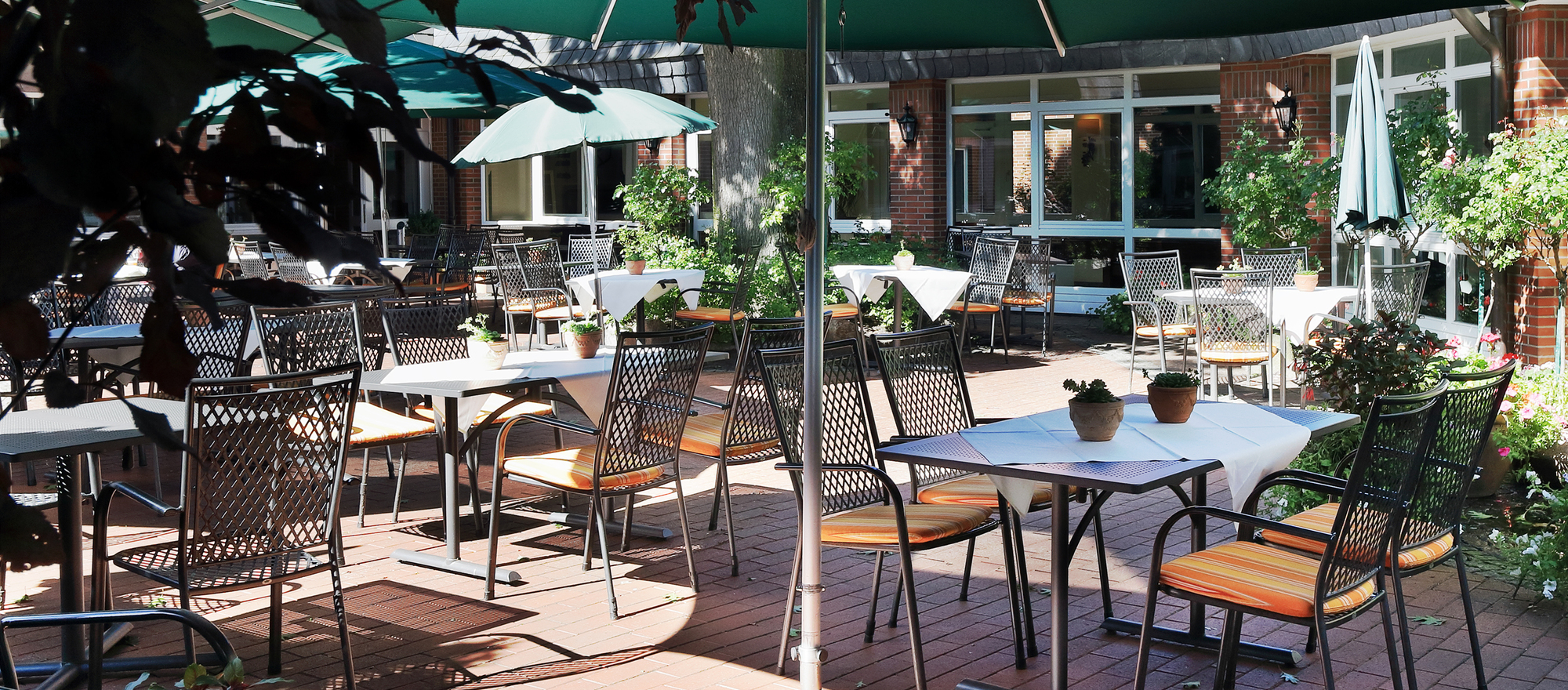 Garden restaurant with sunshades at the 4-star hotel Ringhotel Sellhorn in Hanstedt